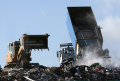 stock-photo-5619965-landfill-garbage-bulldozer-processing-rubbish-dumped-by-truck-on-site